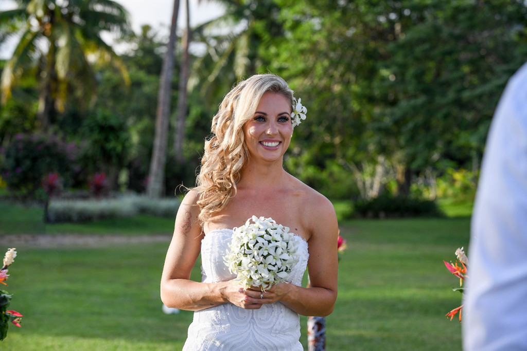 Bride smiles as she walks down the aisle holding her frangipani flower bouquet