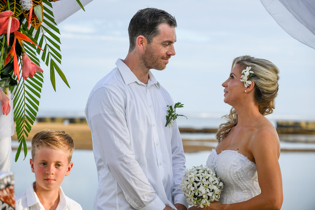 The groom lovingly looks into his bride's eye as he says his vows