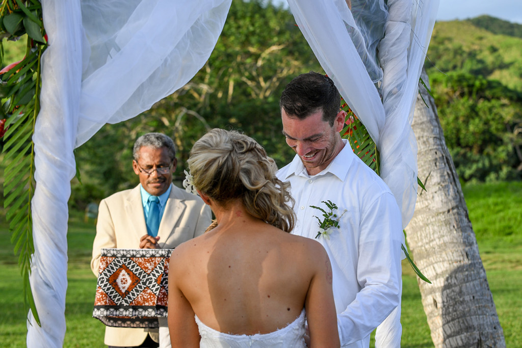Groom smiles as he slips the ring on his bride