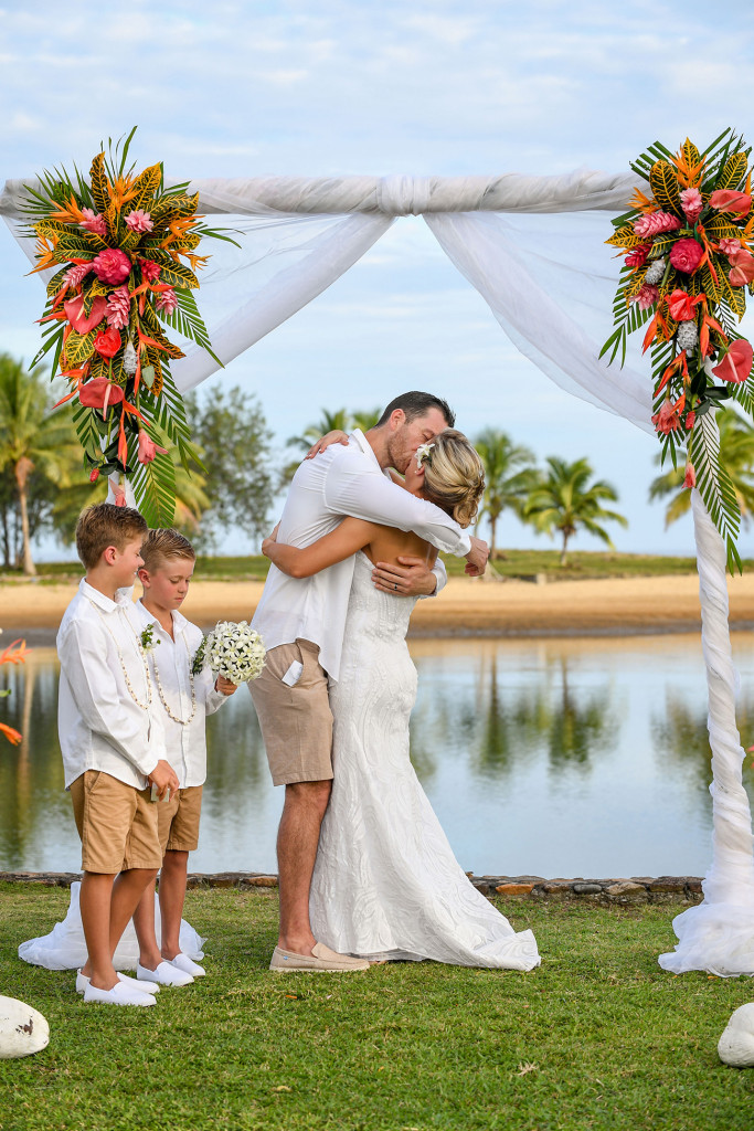 The groom passionately kisses his bride behind the stunning ocean