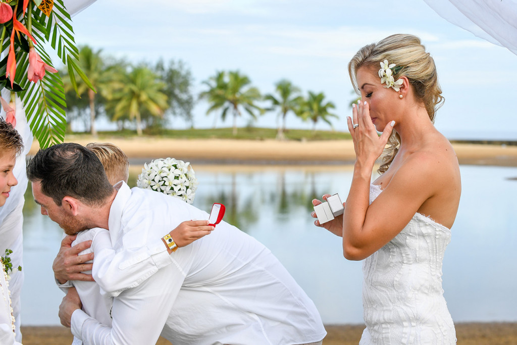 The bride wipes a tear as her groom hugs their sons