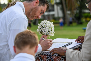 Groom signs marriage certificates