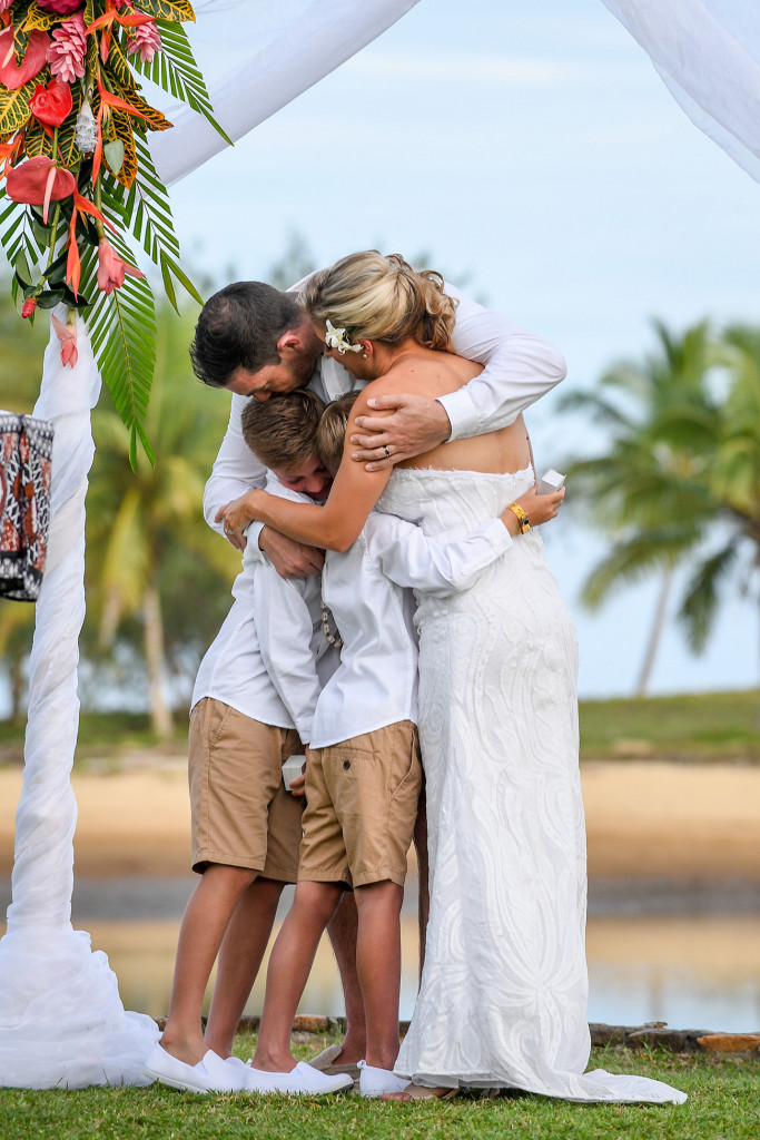 The newly married family embrace in a tight hug after being officially married
