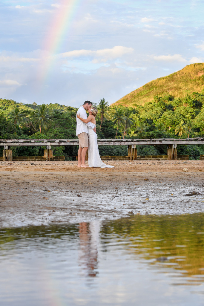 The bride and groom kiss under a rainbow at sunset