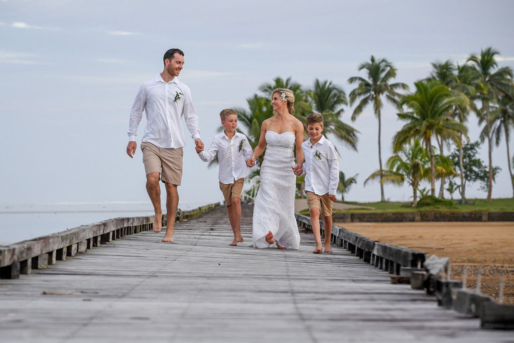 The happily married family walks hand in hand down the dock in Fiji