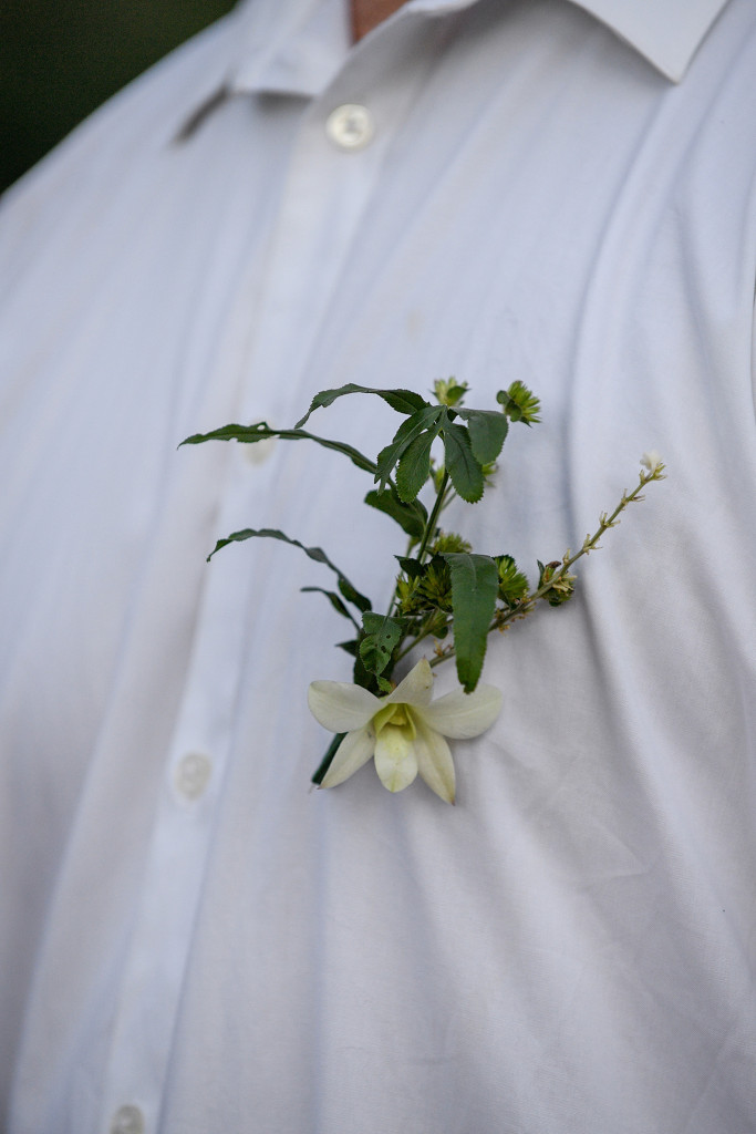 Closeup on groom's frangipani flower boutonniere