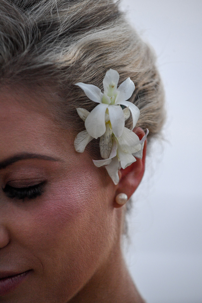 Closeup on frangipani flower tucked behind the bride's hair