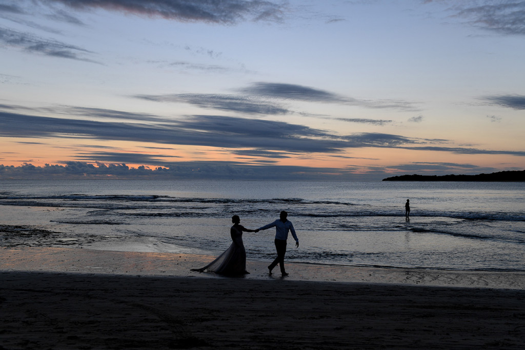 A silhouette of the couple playing in the ocean at sunset