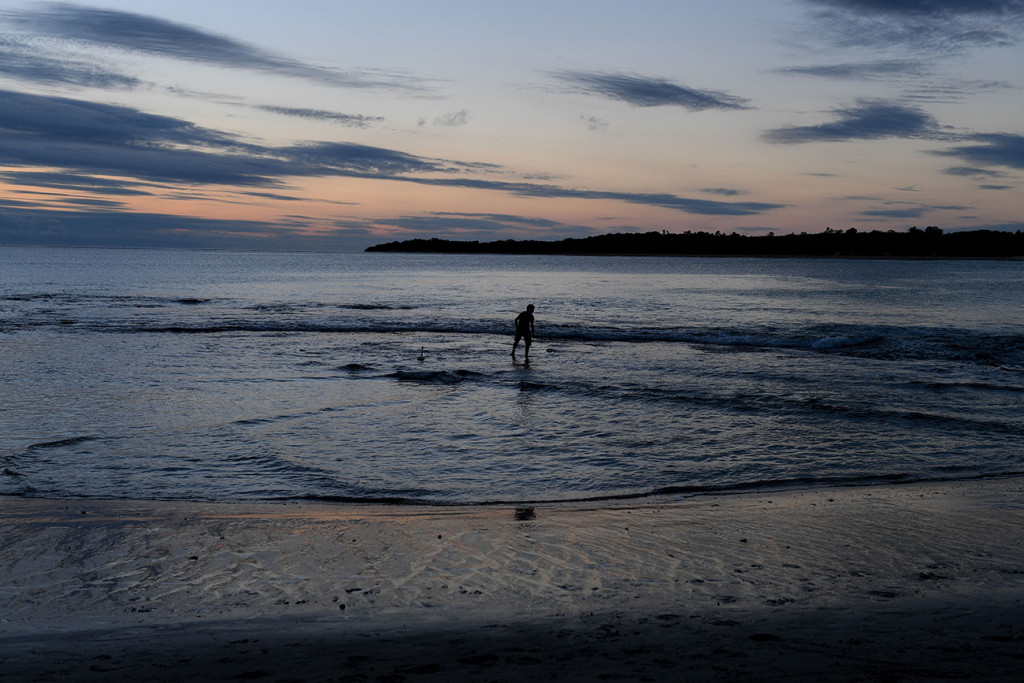 A lone boy plays in the ocean at dusk