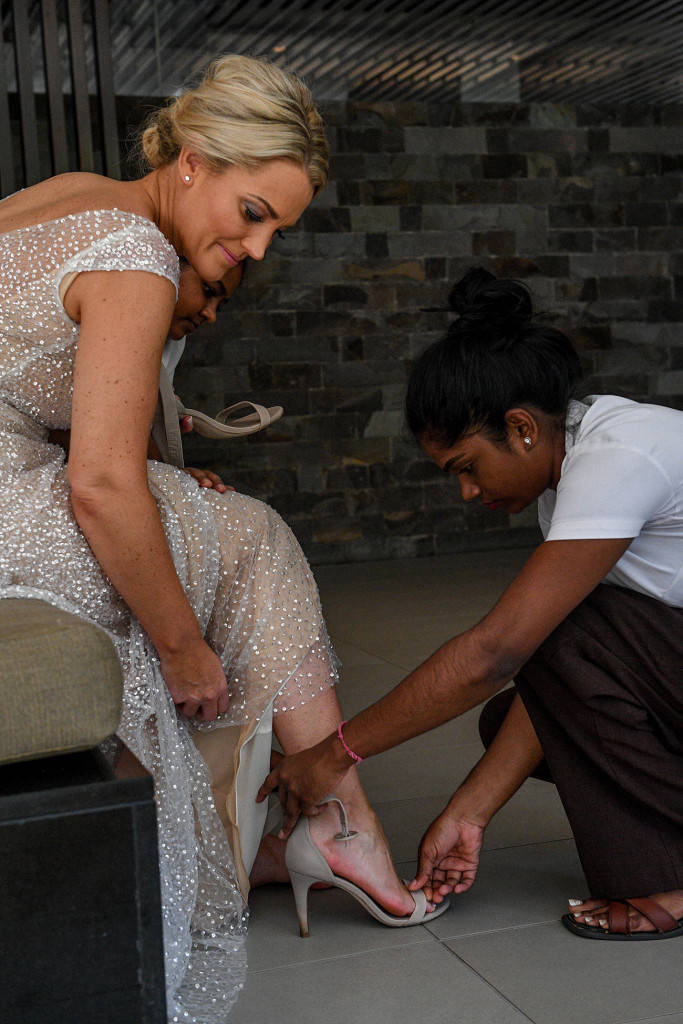The bride ties her Wittner ankle strap, off-white heels