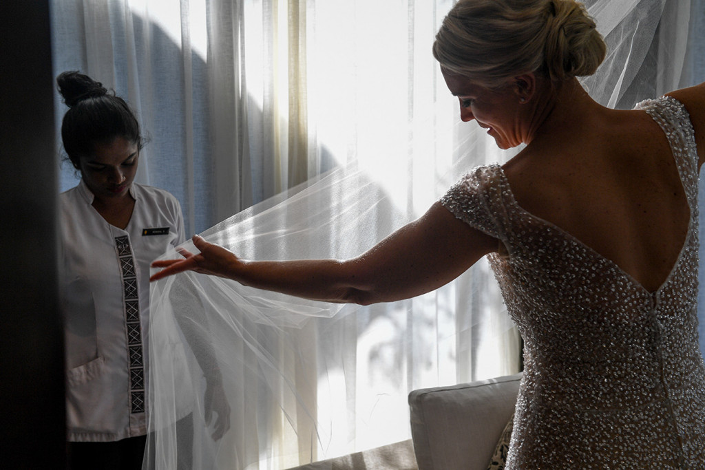 The bride admires her veil in the sunlight.