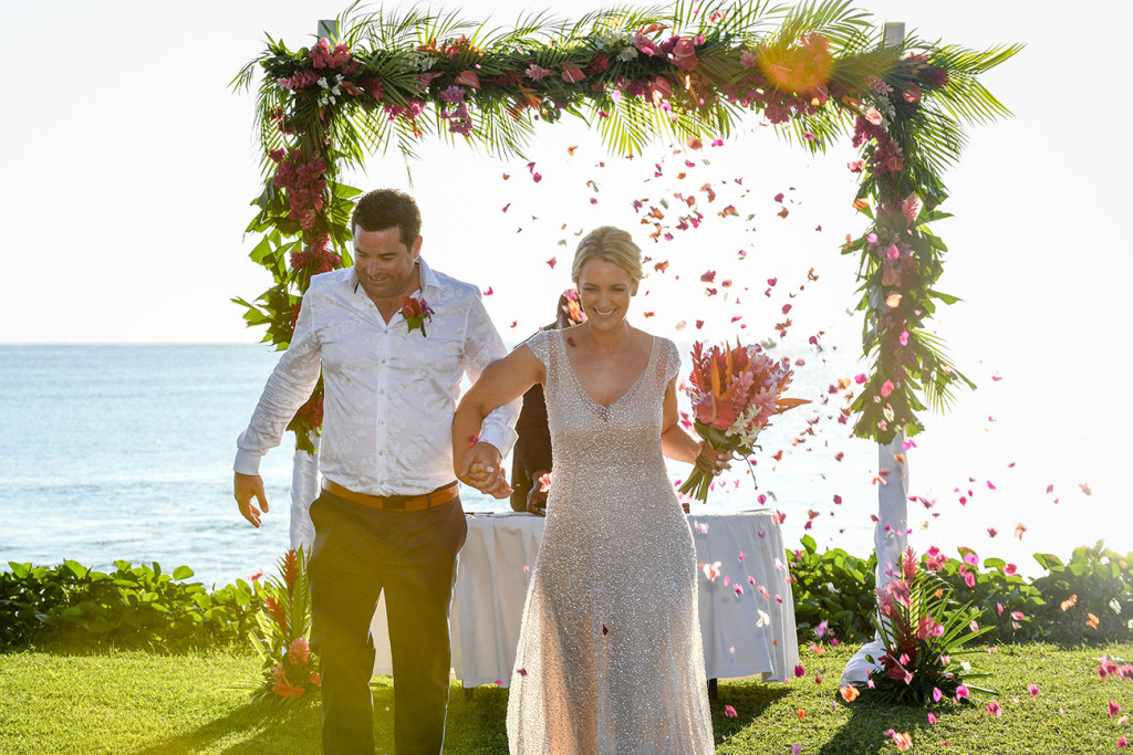 Flowers are strewn on the married couple as they walk from the altar at the beach