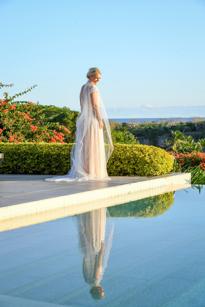The breathtaking bride stares at her reflection in the swimming pool
