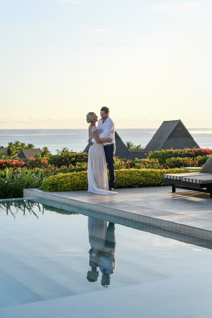 Reflection of the couple in the pool with the stunning Pacific in the background