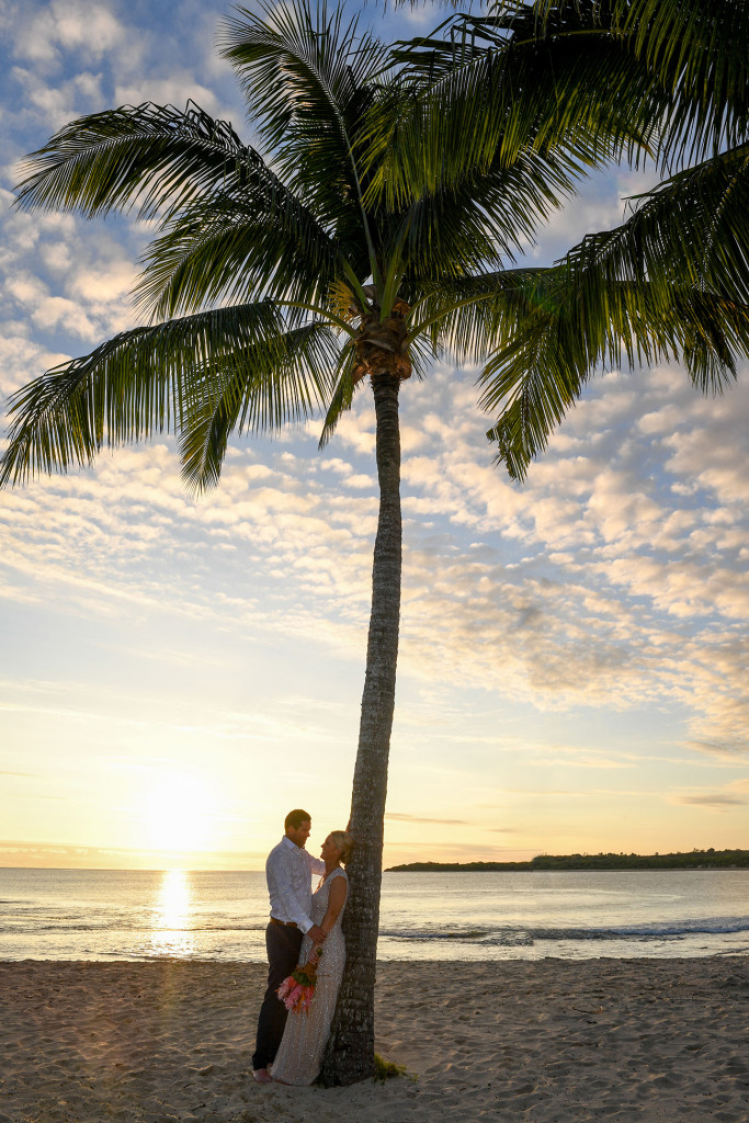The married couple by a palm tree during the glorious sunset in the Pacific ocean