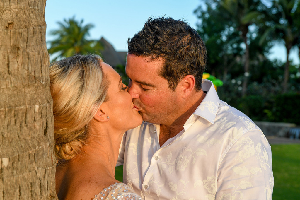 The sun glows on the couple as they kiss against a palm tree