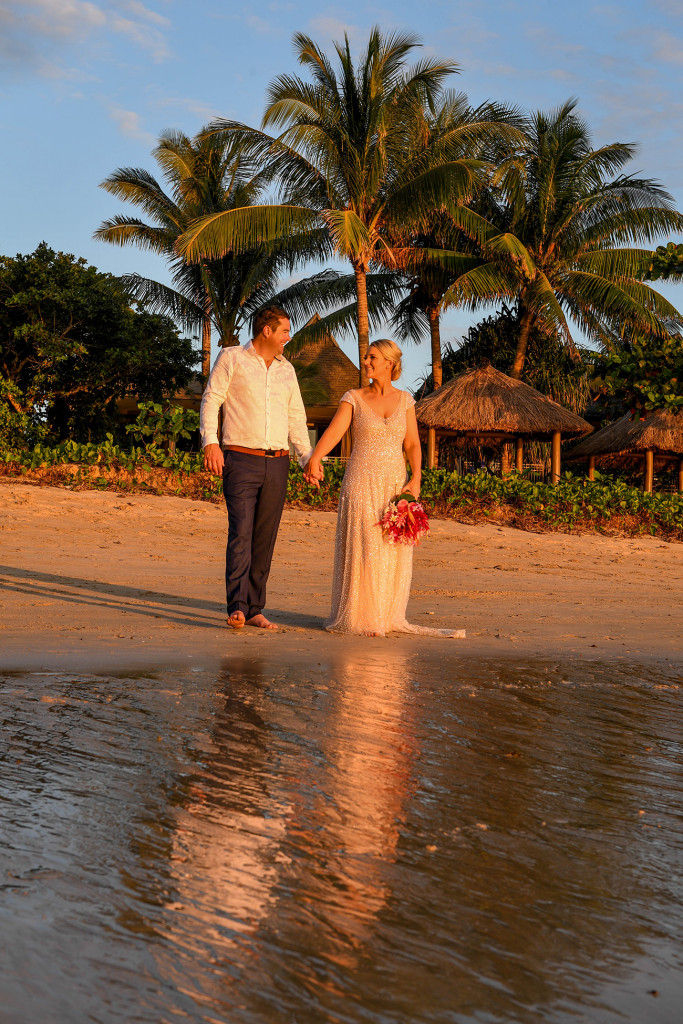 The orange sunset glows on the couple as they walk into the ocean