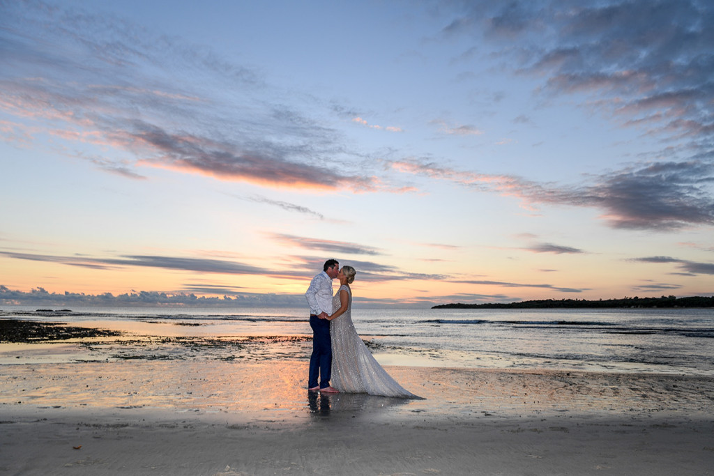 The couple kiss in the foreground of a stunning, pink Fiji sunset