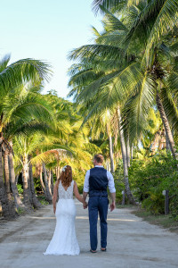 Bride and groom stroll under palm trees