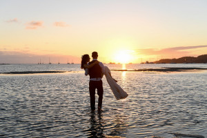 Groom carries bride into sunset