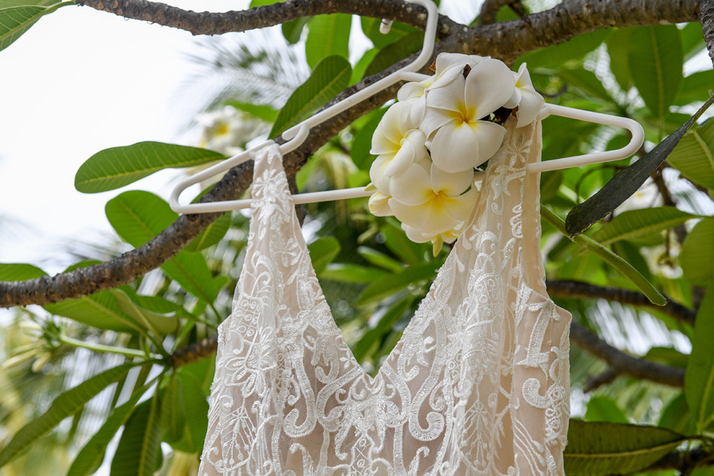 V shaped neckline of dress from Luv Bridal hanging beside a bouquet of tropical Frangipani flowers
