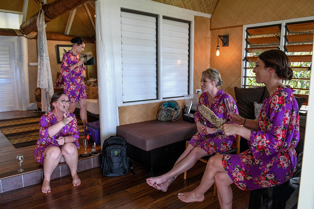 Bridesmaids in floral purple kimonos while preparing for the wedding