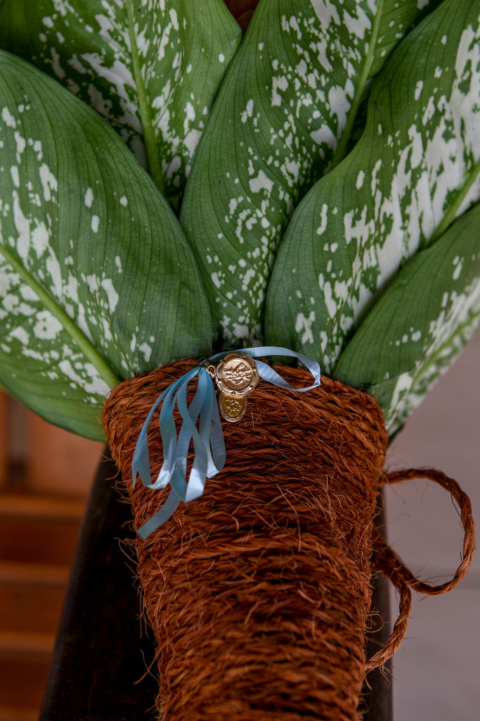 Traditional family medallion (something blue) draped on green and white ferns