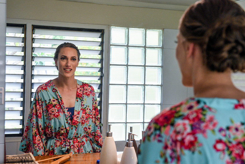 The stunning bride in a floral, blue kimono admires her reflection in the mirror