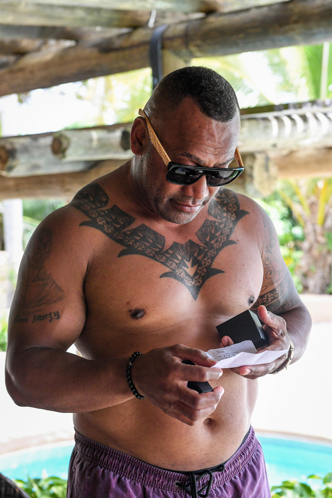 Buff groom with a tradition Fiji neck tattoos reading a note from his bride