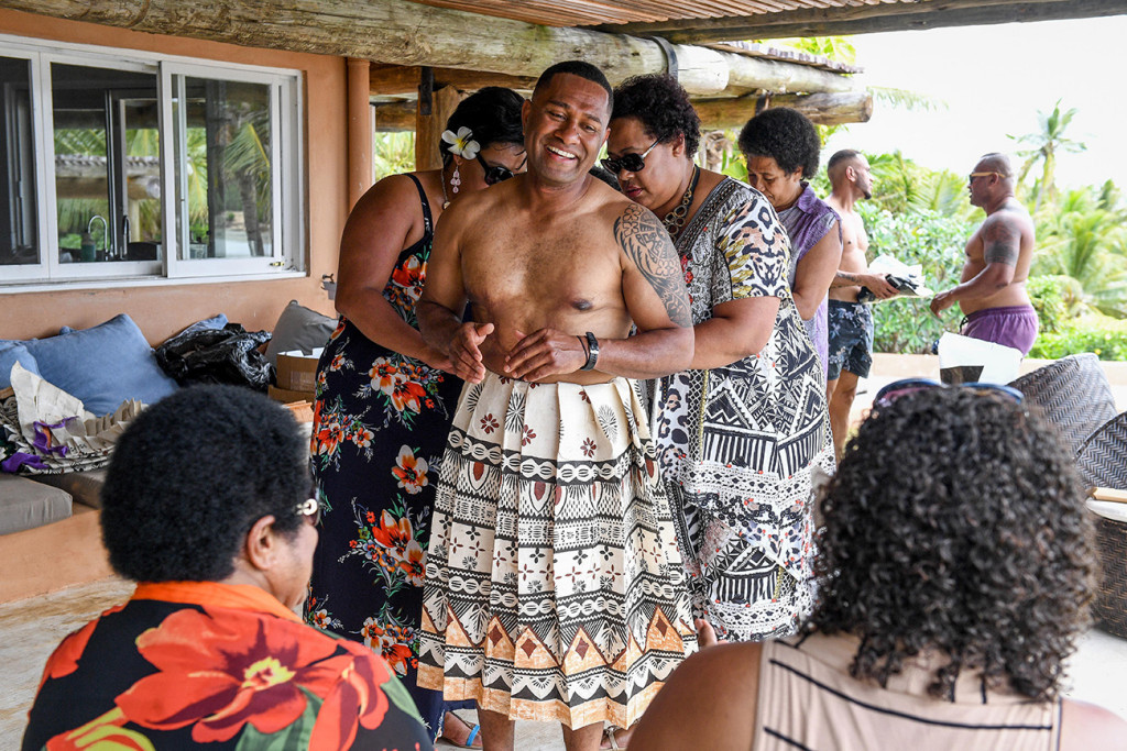 A groomsman laughs as a relative ties a fijian masi around his waist.