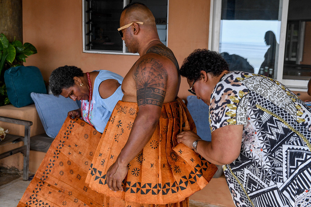 Focussed relatives tie the bow on the traditional groom's colourful Fiji masi skirt