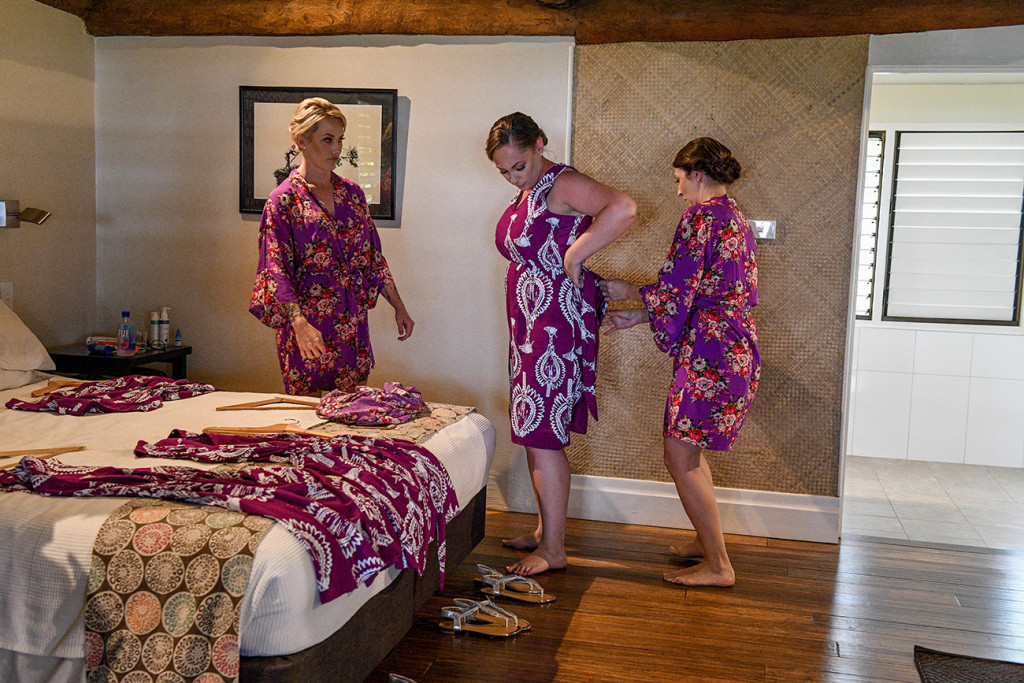 The bridesmaids change out of their purple kimonos into their purple dresses brides dresses