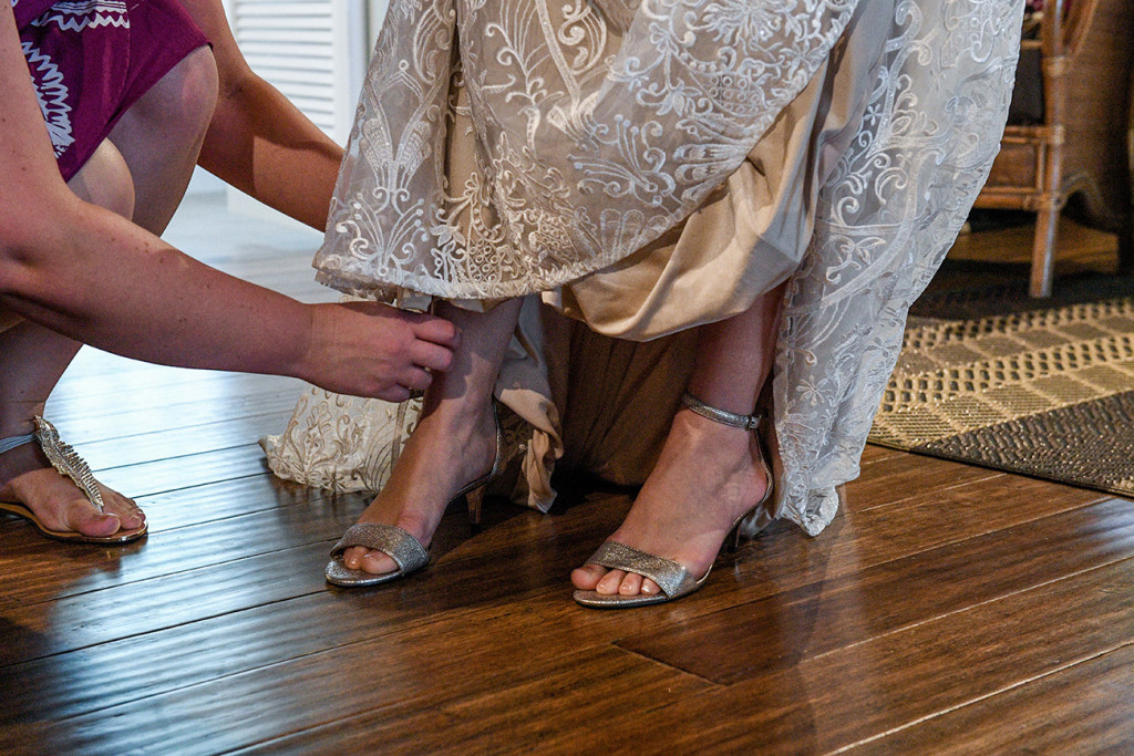 Bride straps into her silver ankle strapped high heels by Nine West