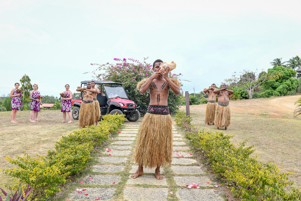 Traditional Fiji groomsmen blow a horn made from a seashell
