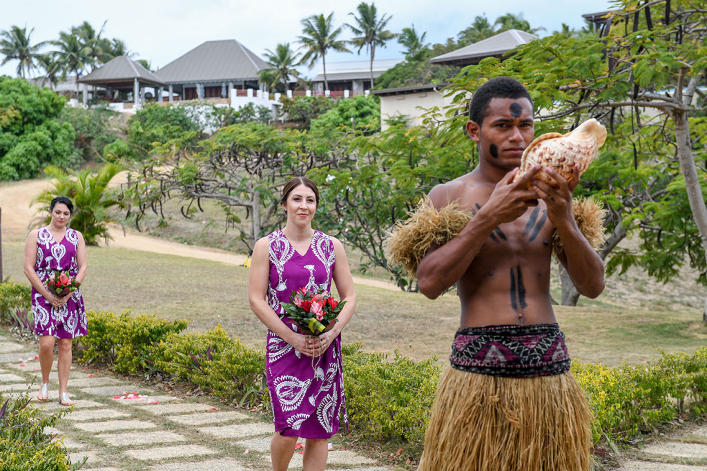 Bridemaid in purple Fiji dress behind traditionally clad Fiji groomsman