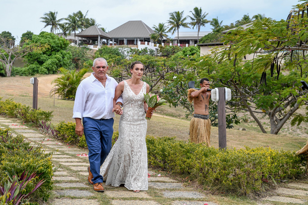 The gorgeous bride walks down the aisle with her father