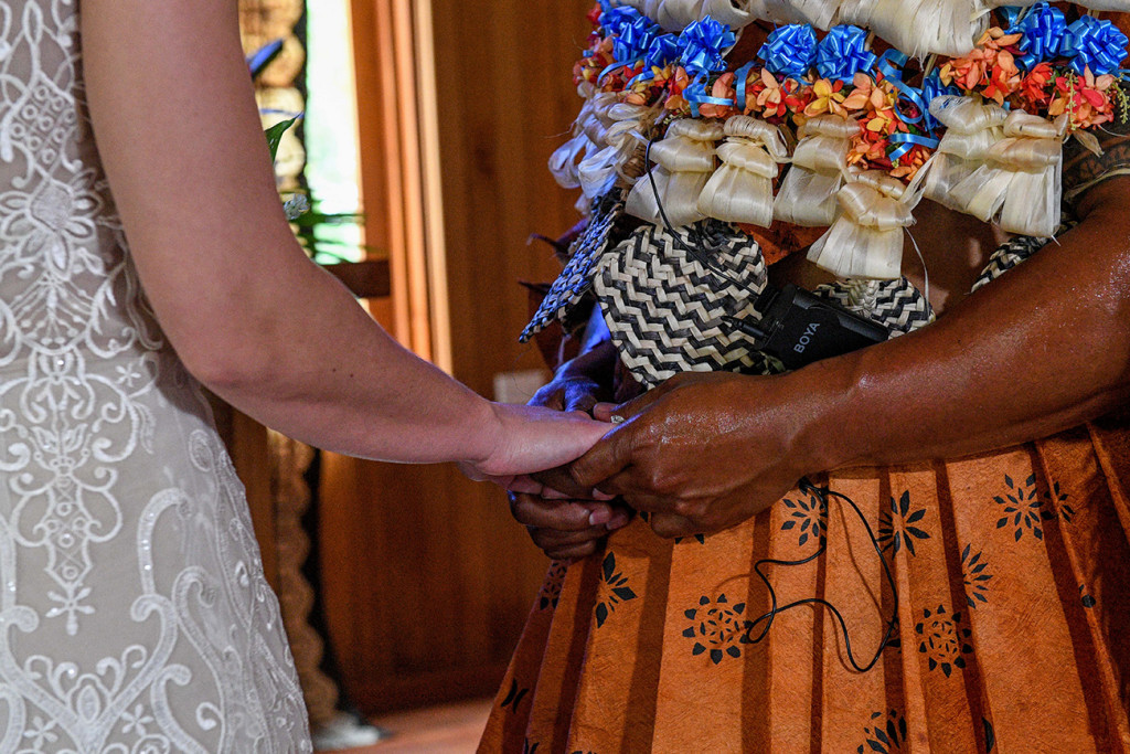 Closeup of groom and bride holding hands at the altar