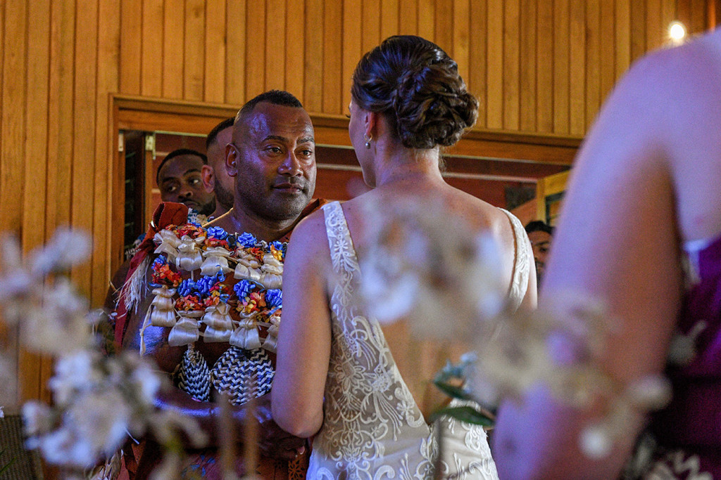 An emotional Fiji groom watches as his bride says her vows