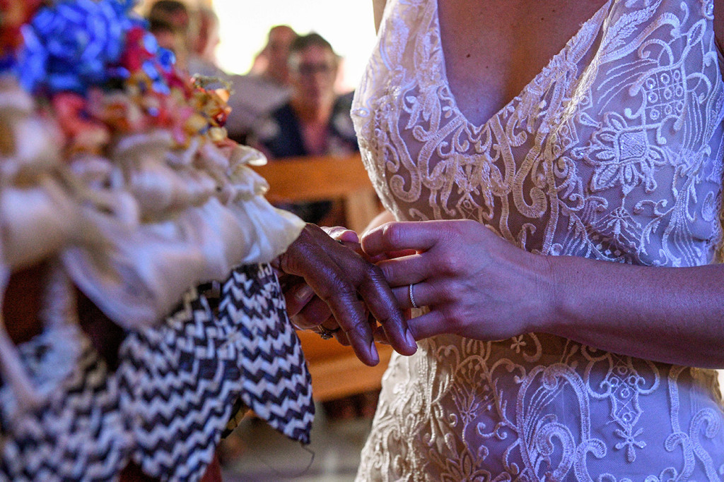 Closeup of the bride slipping the silver wedding ring onto her groom
