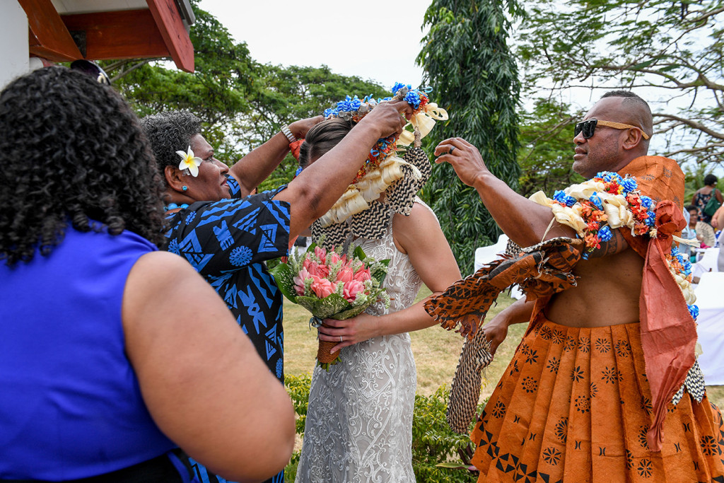 The groom's family dresses the bride with a traditional Fiji wreath