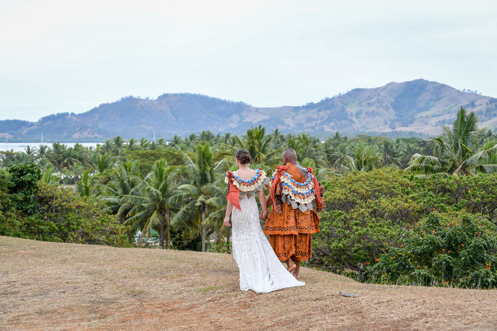 The newly married couple walks toward palm trees that litter the breathtaking Fiji landscape