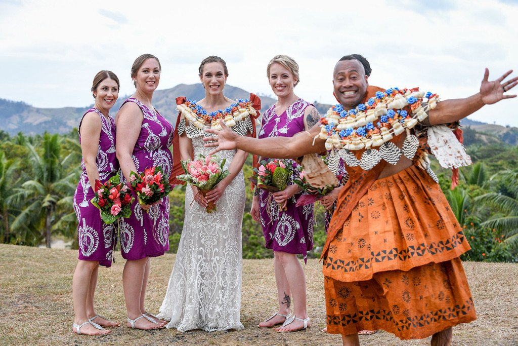 The groom photobombs the bridesmaids with a cheeky smile
