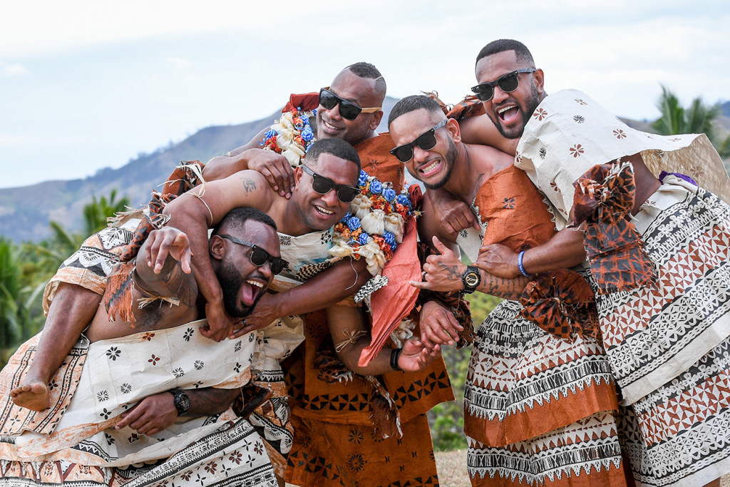 The Fiji groom and his groomsmen jump into a gigantic group hug