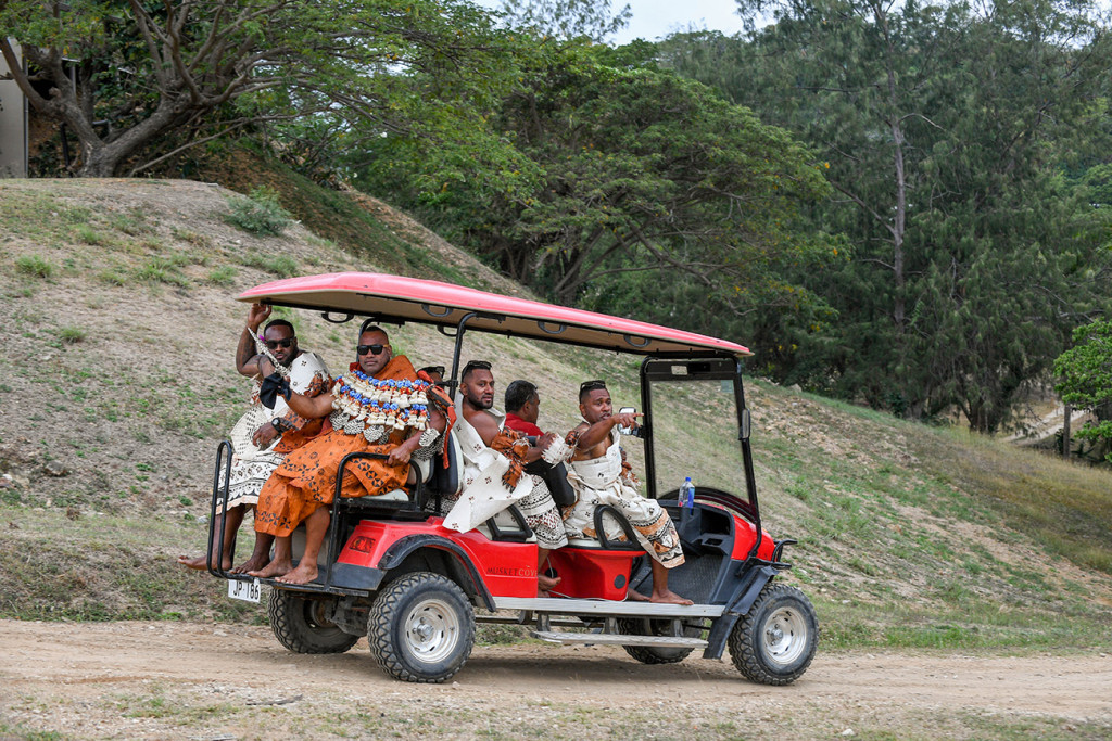 The groom and his groomsmen ride up in a red golf cart