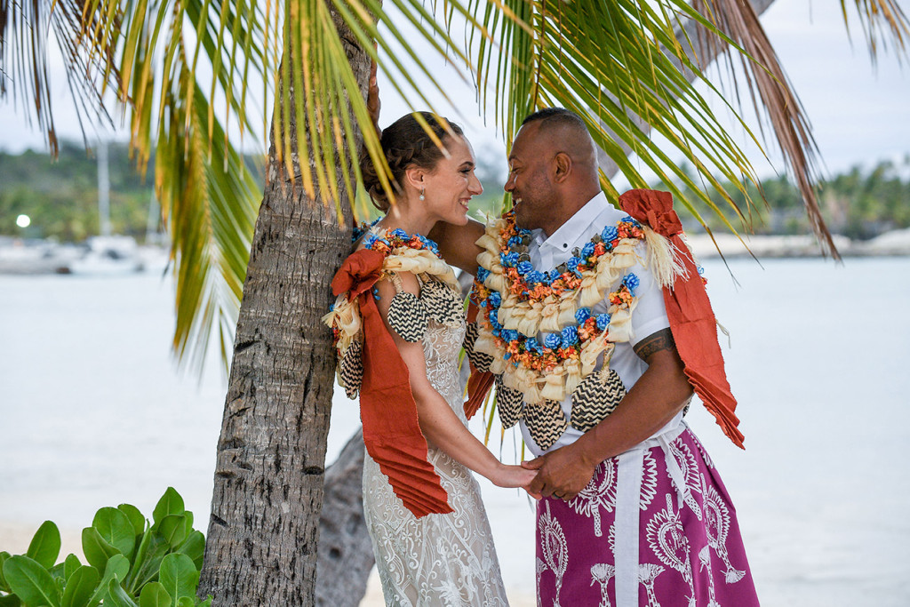 The bride and groom share a passionate moment under the palm tree