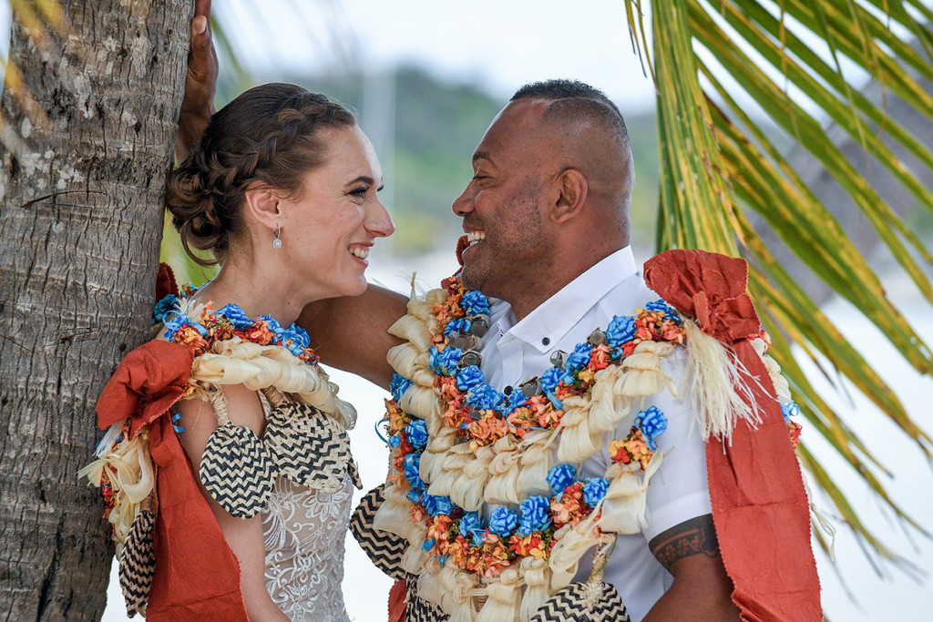 The bride and groom laugh with each other while under a palm tree
