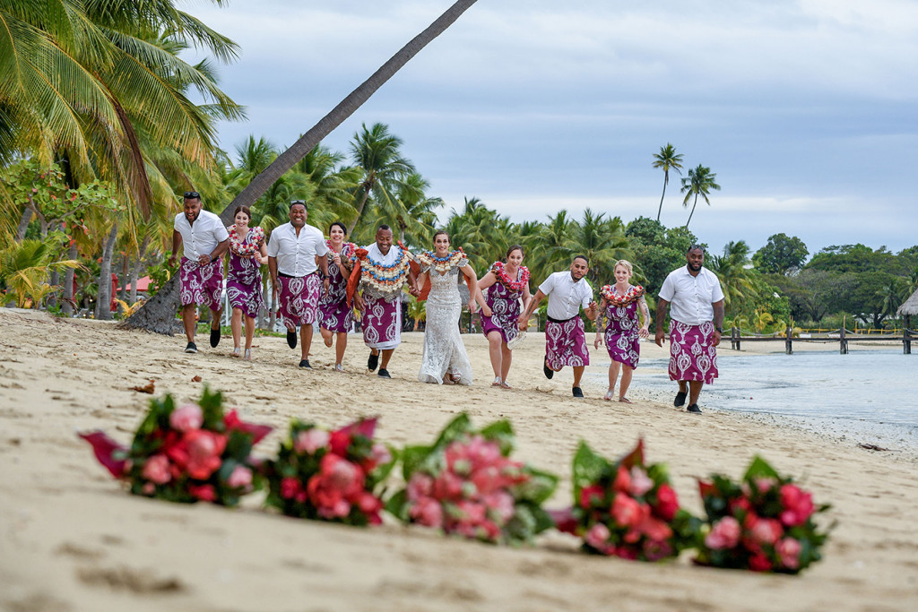 The bridal party runs towards the camera with ginger bouquets in the foreground