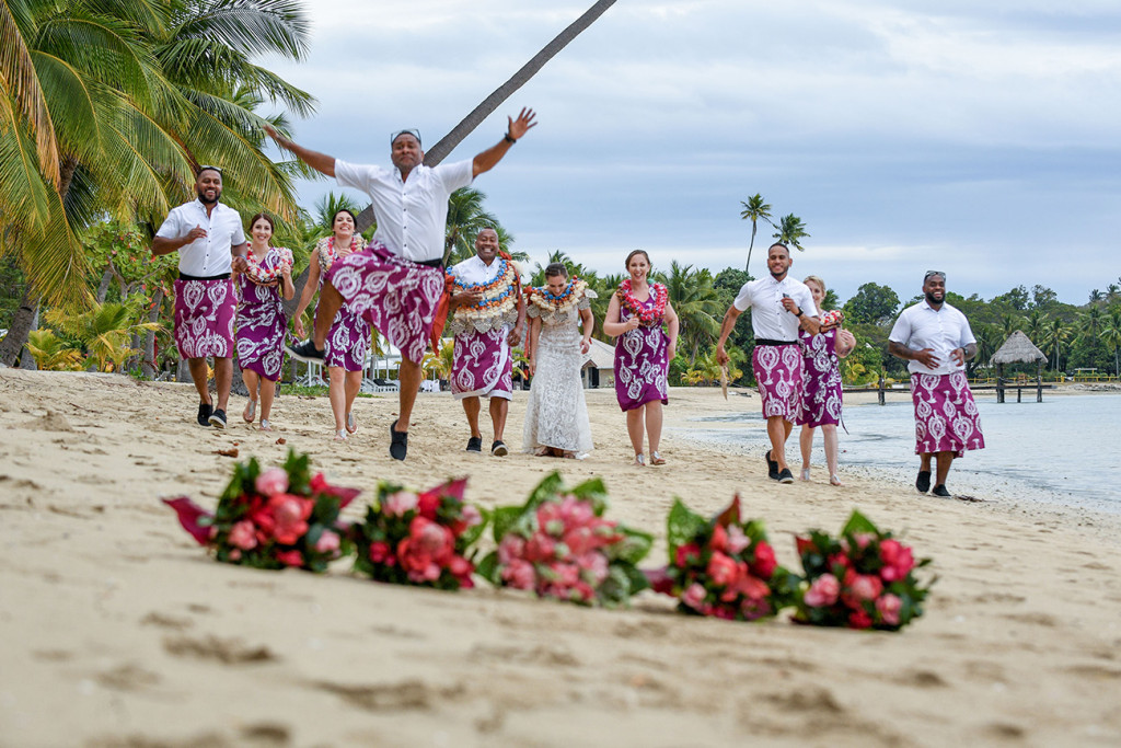 A groomsman leaps into the air while running towards the camera on the beach