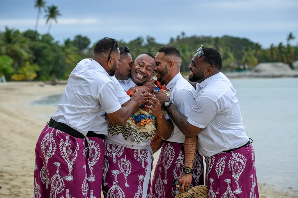 The groomsmen cheekily cuddle and kiss the groom at the shores of the Pacific