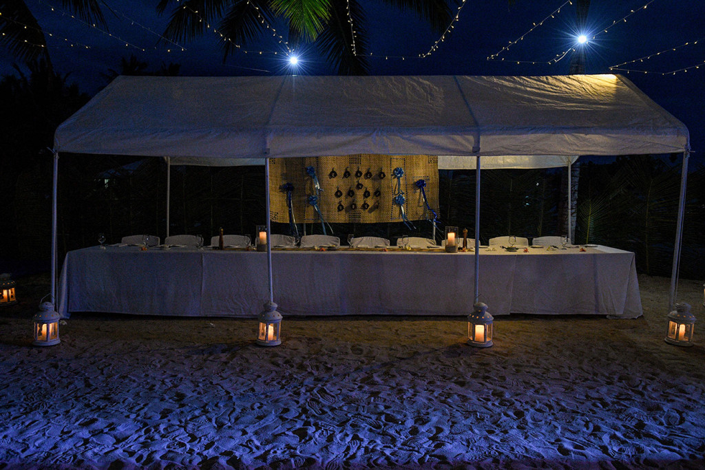 An intimate wedding reception setup on the beach under the stars with fairy lights and lanterns